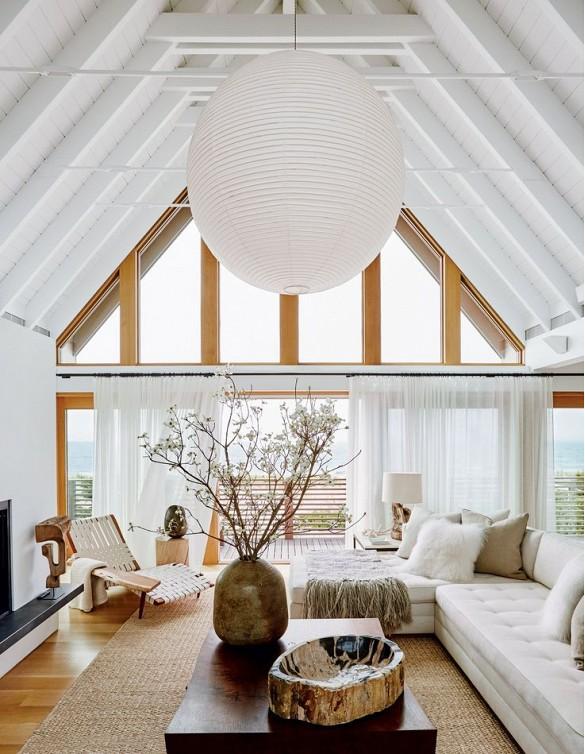 El living cuenta con enormes ventanales, una linterna de papel y colores neutros para los muebles y la decoración, incluso una escultura africana, un recipiente de madera petrificada de Inglaterra y un jarrón de cerámica de Tailandia.