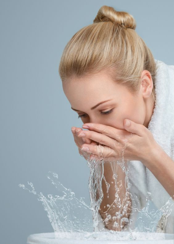 Young woman washing her face and hands with clean water in the morning
