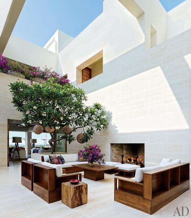 CRAWFORD. El árbol frangipani le da un toque al patio con mesas de teca y asientos hechos a medida, cojines tapizados de Ralph Lauren Home y Josh Robshaw.