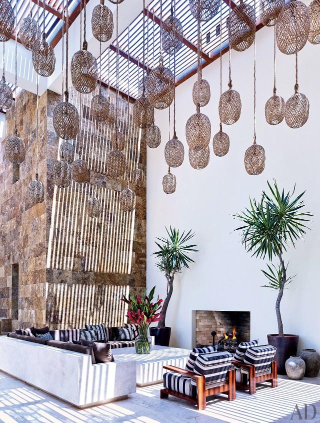 CLOONEY. Linternas hechas de cordeles, mesa de cemento y yeso y un sofá hecho a medida con cojines de Holly Hunt: así es el patio.