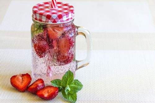 mineral water with strawberries, ice and mint in a vintage cup